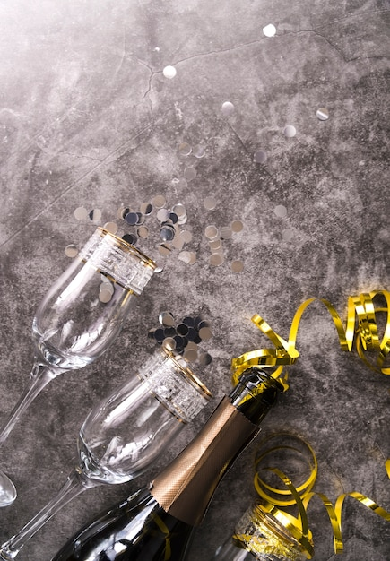 Empty glass and champagne bottle with party decorative item on concrete textured background Free Photo