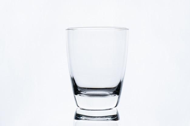 白い壁に分離された水の空のグラス Premium写真