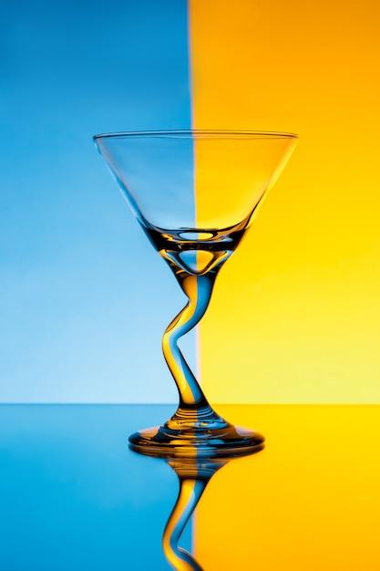 Пустой стакан над синей и желтой стеной Бесплатные Фотографии