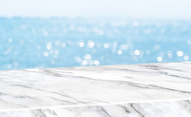 Empty glossy white marble table top with blur sky and sea boekh background Premium Photo