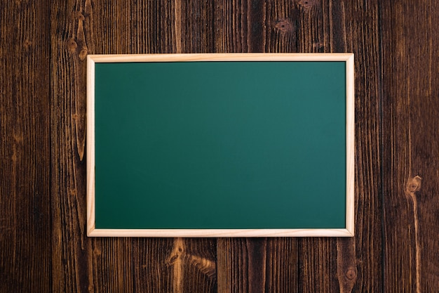 Empty green chalkboard with wooden frame on wooden desk Premium Photo