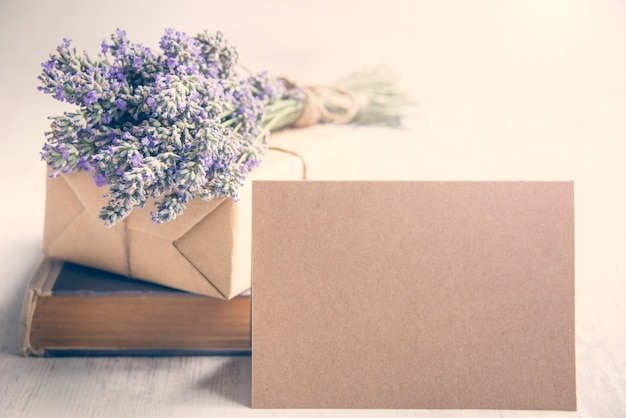 Empty greeting ktaft card infront of a lavender bouquet, wrapped gift and old book over a white wood background. Premium Photo