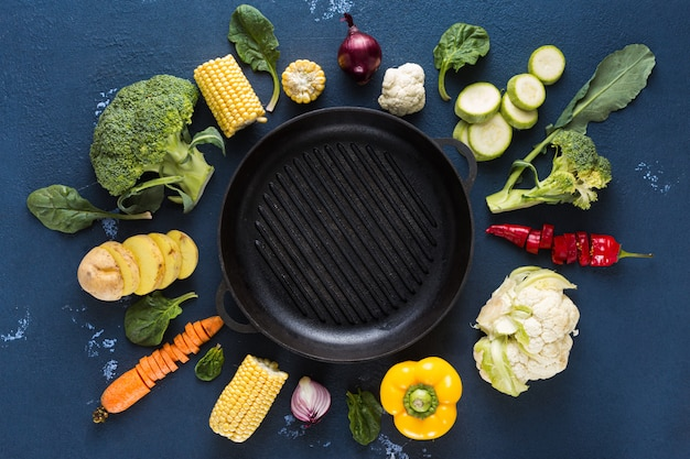 Empty grill pan with fresh vegetarian various ingredients for cooking vegan grilled food overhead view Premium Photo