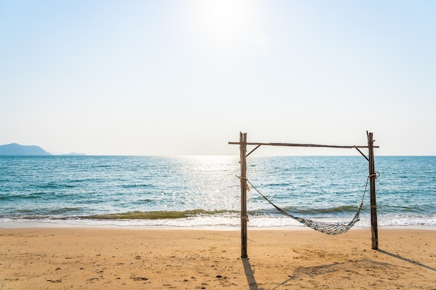 Empty hammock swing on the beautiful beach and sea Free Photo