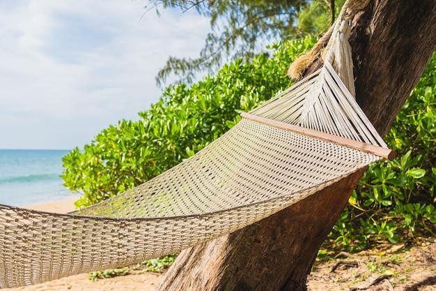 L'amaca vuota sull'oceano del mare della spiaggia tropicale per il tempo libero si rilassa nel viaggio di vacanza Foto Gratuite