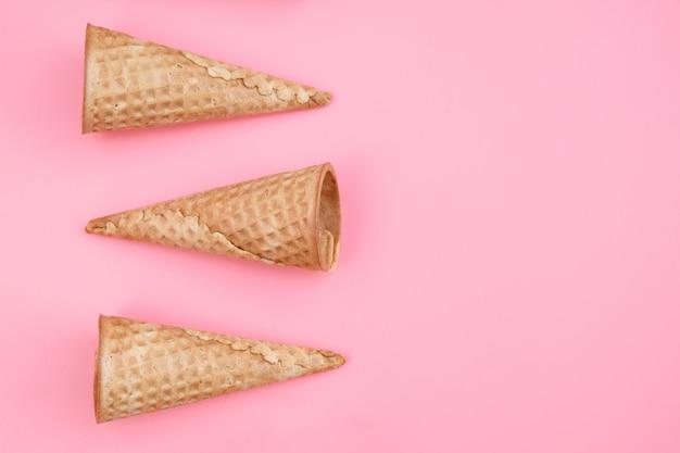 ピンクの背景の空のアイスクリームワッフルコーン。フラット横たわっていたトップビュー。最小限の装飾的な休日のコンセプト。 Premium写真