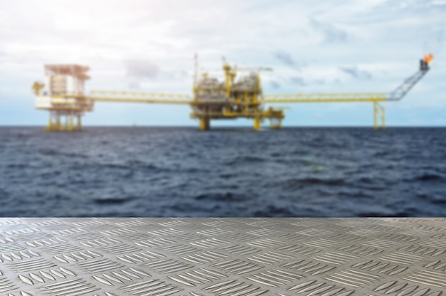 Empty iron plate table with oil and gas platform or construction platform offshore rig blur background for presentation and advertorial. Premium Photo