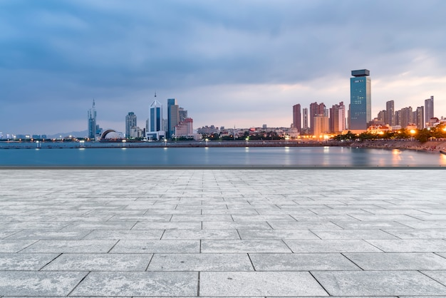 The empty marble floors and the skyline of qingdao's urban buildings. Premium Photo