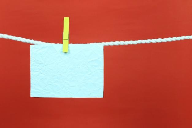 Empty note blue paper hang on the clothesline. Premium Photo