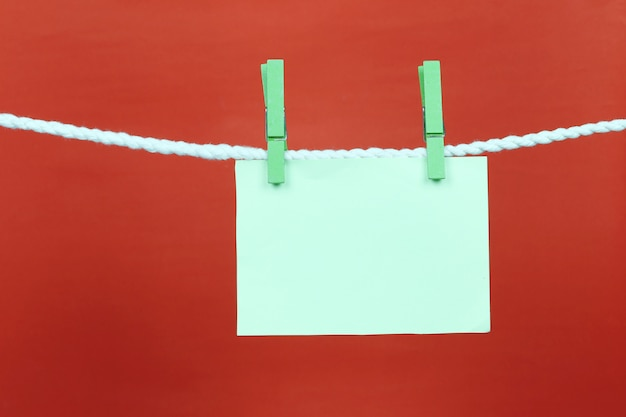 Empty note green paper hang on the clothesline. Premium Photo
