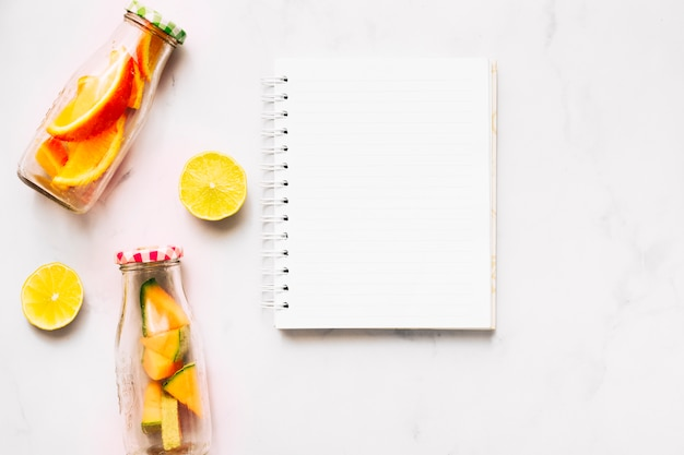 Empty notebook lime and glass bottles with cut citrus Free Photo