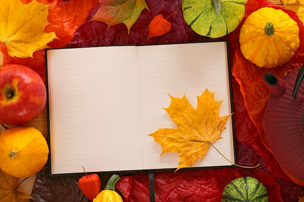 Empty notebook with maple leaf, apples and pumpkins Premium Photo