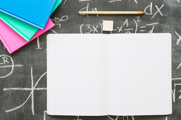 Empty notebook with pen and books on chalkboard Free Photo