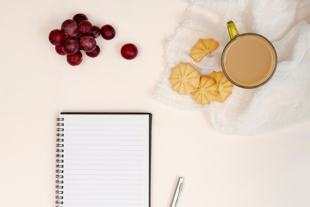 Empty notepad with cookies and grapes Free Photo