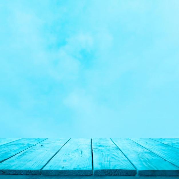 부드러운 하늘 배경에 파란색 나무 테이블 상단의 빈. 몽타주 제품 디스플레이 프리미엄 사진