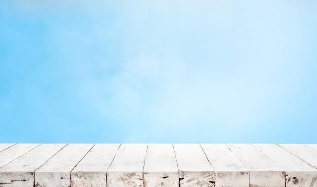 青いパステルカラーの背景に木製のテーブルトップの空。 Premium写真