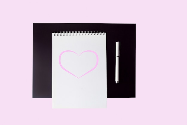 Empty open white with pink heart notebook with pen on pink background top view. Premium Photo