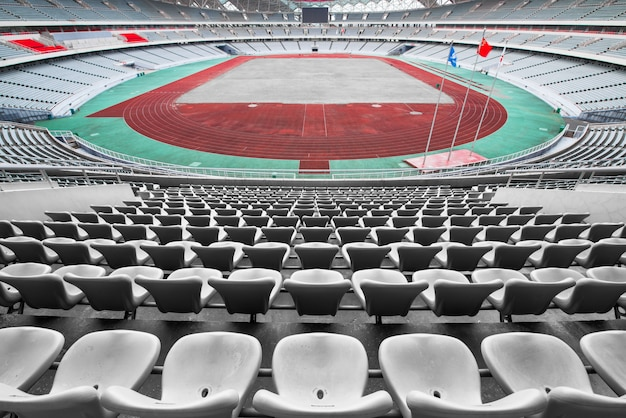 Empty orange and yellow seats at stadium, rows of seat on a soccer stadium Premium Photo