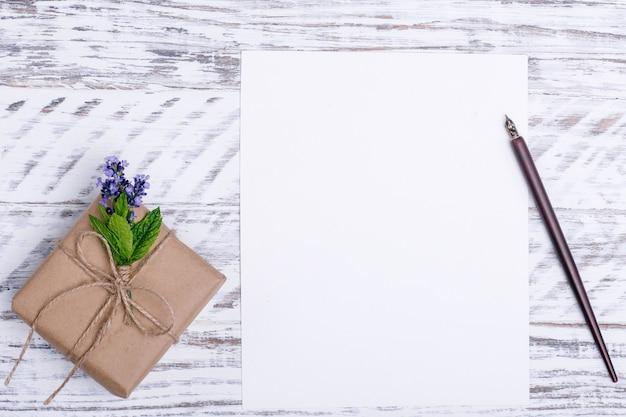 Пустая бумага, цветок, чернильная ручка и подарок на белом деревянном столе. flat lay Premium Фотографии