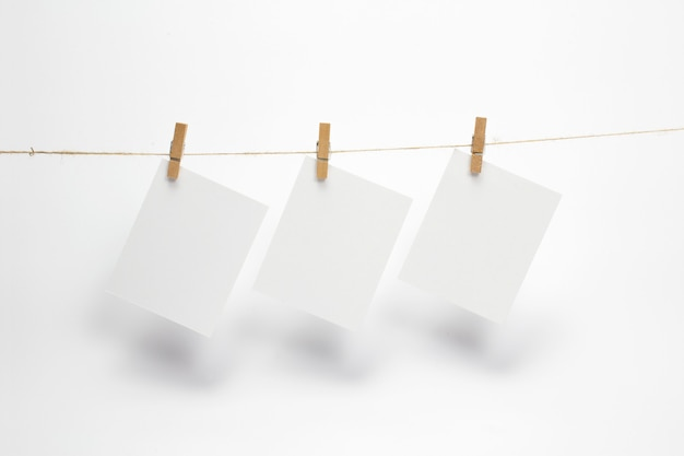 Empty paper frames that hang on a rope with clothespins and isolated on white. blank cards on rope. Free Photo
