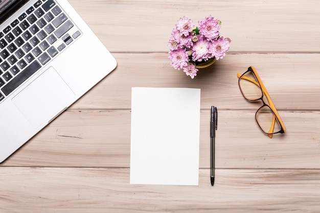 Empty paper sheet pen notebook glasses and flowers on table Free Photo