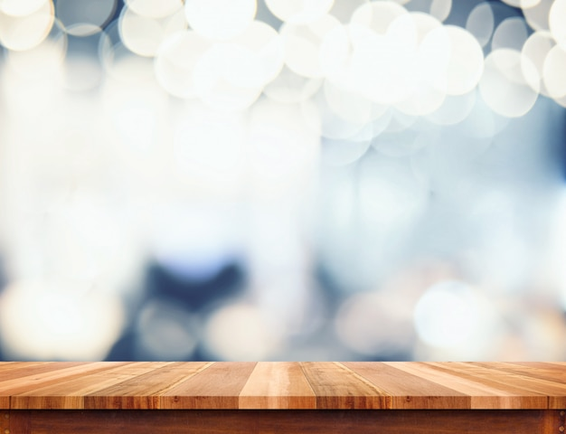 Empty perspective wood plank table top with abstract bokeh light background Premium Photo