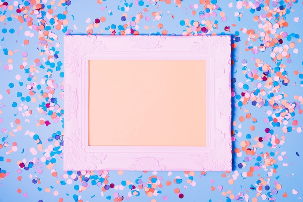 Empty photo frame and decorative confetti on blue background Free Photo