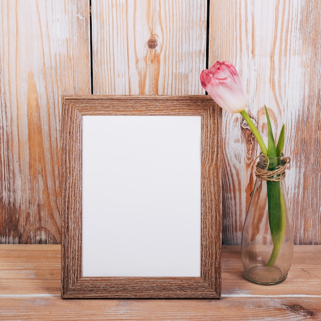 Empty photo frame with single tulip flower in vase on wooden background Free Photo