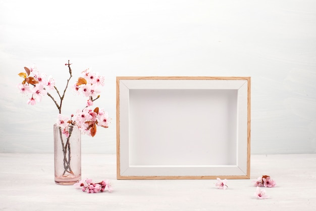 Empty picture frame and pink spring flowers. Premium Photo