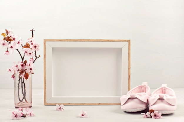 Empty picture frame, pink tender spring flowers and small baby girl shoes Premium Photo