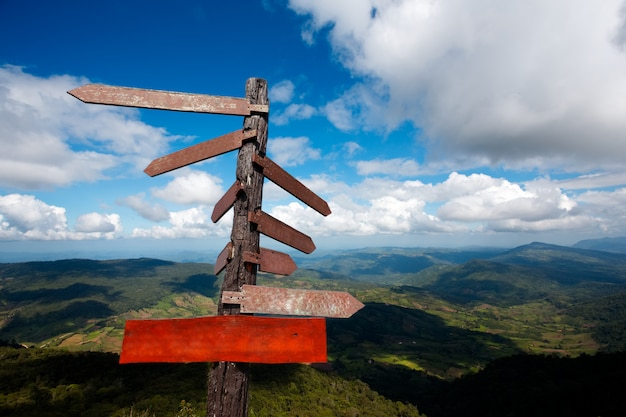 Empty plank and wood guide post on the blue sky with mountain background. Premium Photo