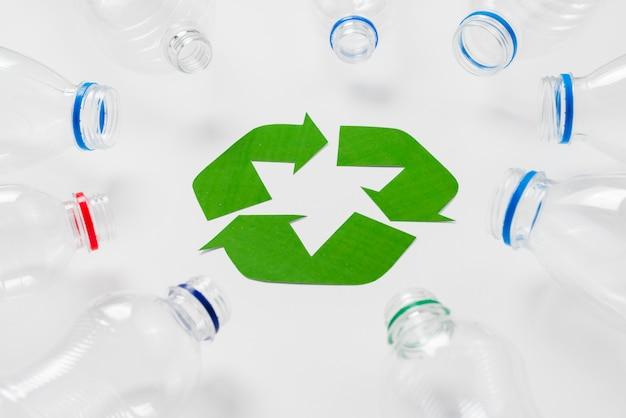 Empty plastic bottles around recycling logo Free Photo