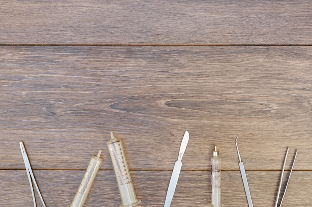 Empty plastic syringe and surgical instruments on wooden desk Free Photo