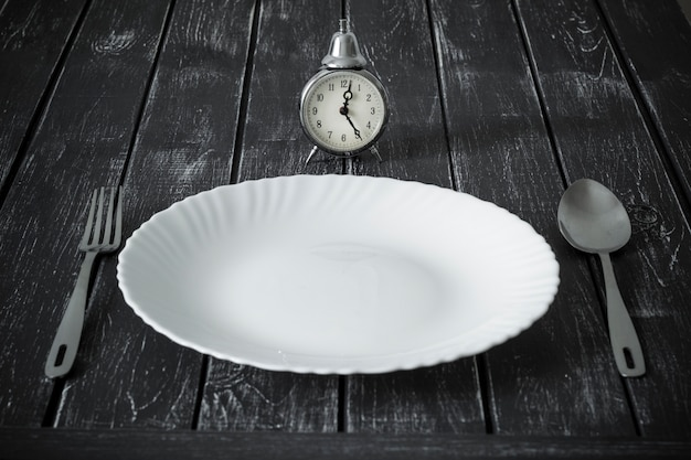 Empty plate and clock with spoon and fork for food. lunchtime. Premium Photo