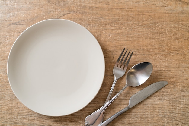 Empty plate or dish with knife, fork and spoon on wooden table Premium Photo