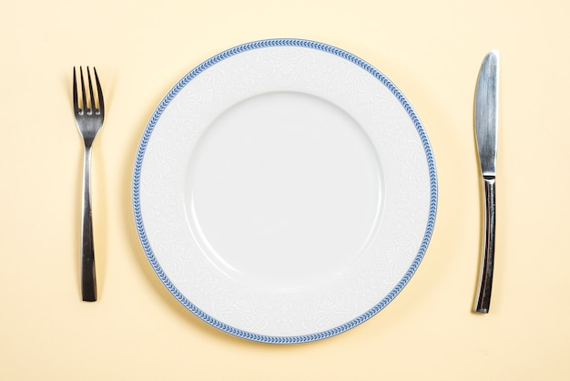 An empty plate between the fork and butter knife on beige backdrop Free Photo