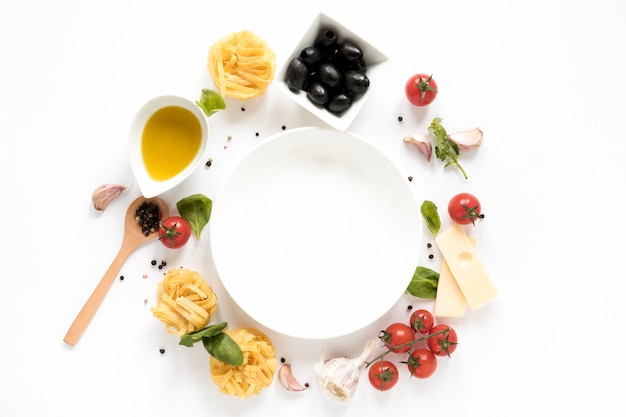 Empty plate surrounded with italian pasta ingredient and wooden spoon isolated on white background Premium Photo