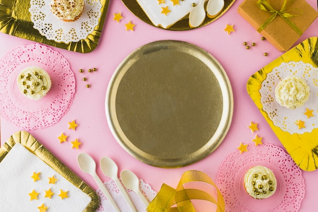 Empty plate surrounded with muffins on decorative pink background Free Photo