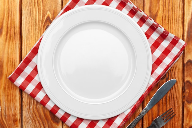 Empty plate and towel over wooden table Premium Photo