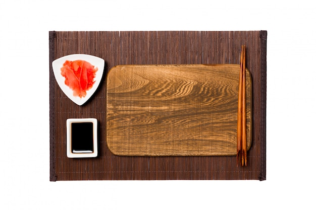 Empty rectangular brown wooden plate with chopsticks for sushi, ginger and soy sauce on dark bamboo mat . top view with copyspace Premium Photo