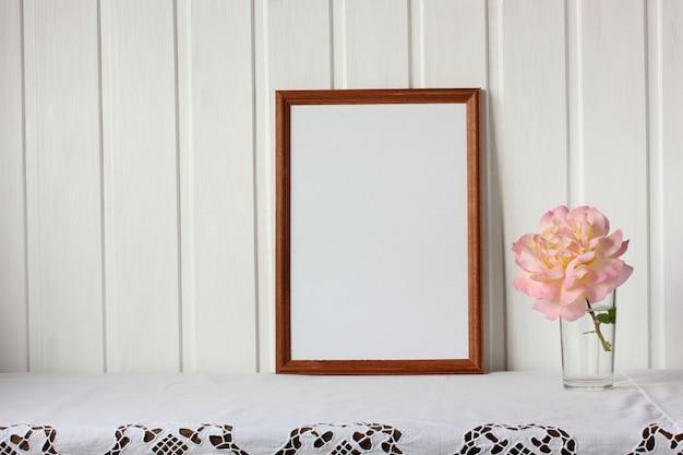 Empty rectangular frame and a rose flower. mockup, scene creator. Premium Photo