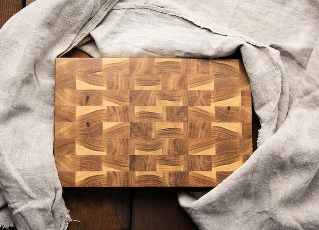 Пустая прямоугольная деревянная разделочная кухонная доска на столе, вид сверху Premium Фотографии
