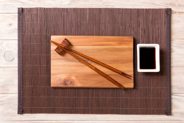 Empty rectangular wooden plate for sushi with sauce and chopsticks on wood Premium Photo