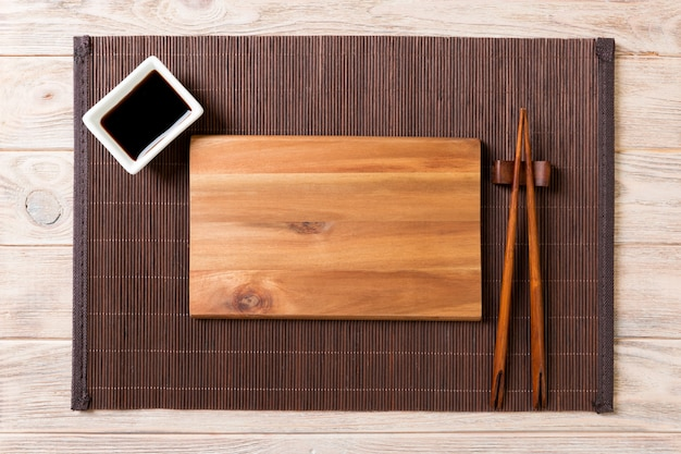 Empty rectangular wooden plate for sushi with sauce and chopsticks on wooden table, top view Premium Photo