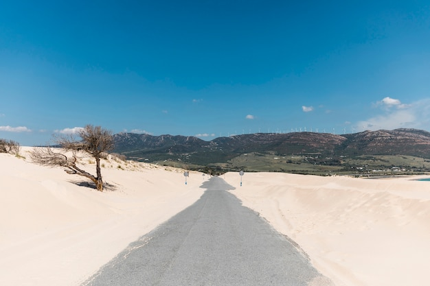 Empty road in sands against mountains Free Photo