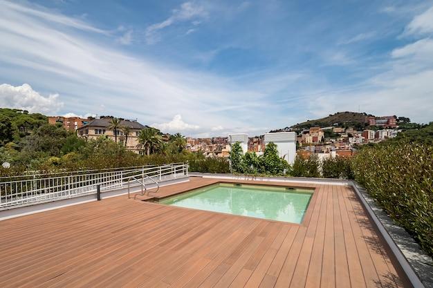 スイミングプール付きの空の屋上。街と山を眺める Premium写真