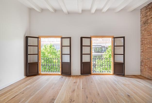 나무 바닥과 두 개의 발코니가있는 빈 방 프리미엄 사진
