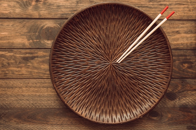 An empty round plate with two wooden chopsticks over the table Free Photo