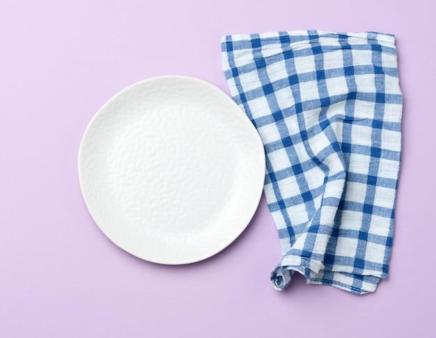 空の丸い白いセラミックプレートと青いナプキン紫の背景 Premium写真