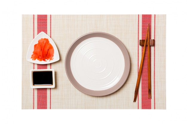 Empty round white plate with chopsticks for sushi and soy sauce, ginger on sushi mat background Premium Photo